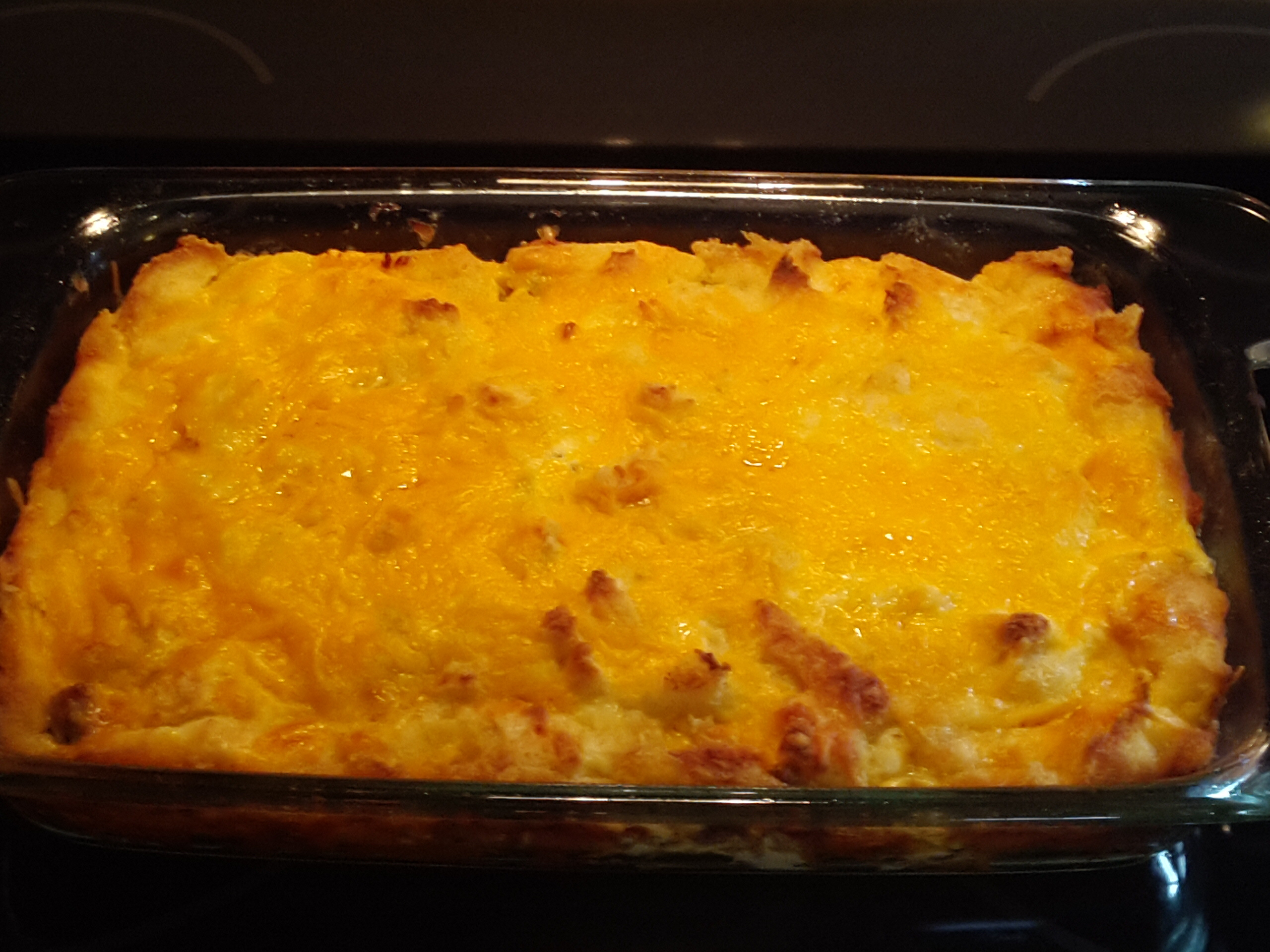 Brown the ground beef with the onions. Add the cream of mushroom soup and one can of water. Pour into a casserole dish. Add the cheddar cheese and the tater tots and stir. Sprinkle the mozzarella cheese on top. Bake at degrees for minutes or until cheese is lightly brown.