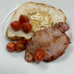 Egg in the hole with bacon and tomato